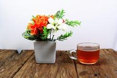 Biała waza z pomarańcze biali kwiaty i herbata na w filiżanka - Obrazy Stock
