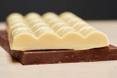 Biała wyśmienicie porowata czekolada kłama na czarny jeden Fotografia Stock