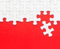 Biała wyrzynarki łamigłówka na czerwonym tle Fotografia Stock