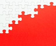 Biała wyrzynarki łamigłówka na czerwonym tle Obraz Royalty Free