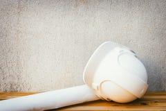 biała zbawczego hełma papieru i klingerytu rolki planu projekta budowa inżynieria na drewnianej podłoga zgłasza tło rocznika Zdjęcia Royalty Free