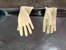 Białe gumowe rękawiczki wystawiać na stali nierdzewnych fenders Używać moczą gumowe rękawiczki obraz stock