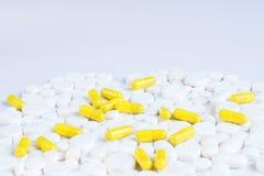 Białe i żółte pigułki na białym tle obraz stock