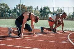 Białe i czarne męskie atlety przygotowywają zaczynać obrazy stock