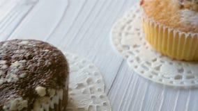 Białe i czekoladowe babeczki na białym drewnianym stole Ostrość od jeden inny zdjęcie wideo