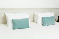 Białe i zielone poduszki na łóżku Obrazy Royalty Free