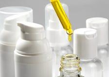 Białe kosmetyczne butelki z zdroju kosmetyka olejem Wellness, zdrój i ciało, dbamy butelki kolekcję kąpielowy piękna składu olej  Fotografia Stock