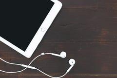 Białe pastylki komputerowej muzyki słuchawki na ciemnym brązie zgłaszają backgr obraz stock