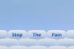 Białe pigułki na błękitnym tle z słowa ` Zatrzymują Bólowy ` obrazy royalty free