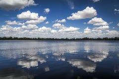 Białe puszyste chmury odbija w jeziorze Obraz Stock