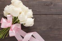 Białe róże kwitną z faborkiem są na drewnianym tle Fotografia Royalty Free