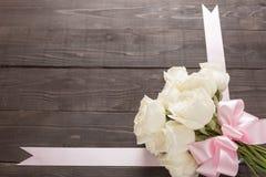 Białe róże kwitną z faborkiem są na drewnianym tle Obraz Stock