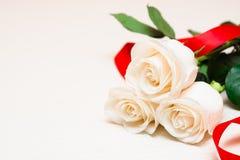Białe róże z czerwonym faborkiem na lekkim drewnianym tle Women Zdjęcia Stock