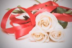 Białe róże z czerwonym faborkiem na lekkim drewnianym tle Women Fotografia Royalty Free