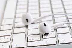 Białe słuchawki na białej klawiaturze obrazy stock