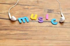 Białe słuchawki z słowo muzyką fotografia stock