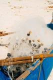 Białe sieci rybackie w błękitnej łodzi na plaży Zdjęcie Royalty Free