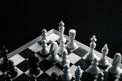 Białe szachowe postacie bronią przeciw czarnym postaciom na chessboard zdjęcie stock