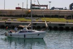 Białego żeglowanie jachtu wchodzić do port Walencja, Hiszpania Fotografia Royalty Free