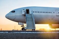 Białego ciała pasażerski samolot z abordażu krokami przy lotniskowym fartuchem w wieczór słońcu zdjęcie stock