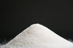 Białego cukieru rozsypisko na czarnej tła zbliżenia fotografii fotografia royalty free