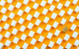 Białego cukieru sześciany z jeden brown cukieru sześcianami na pomarańczowym tle obraz stock