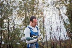 Białego człowieka budowniczy pracuje z kurendą zobaczył outdoors, portret fotografia stock