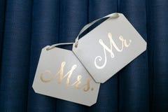 Białego kwadrata plakiety z białymi faborkami i Złotymi inskrypcjami Mr i Mrs odizolowywający na błękitnym tle zdjęcia royalty free