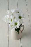 Białego kwiatu Posy w dzbanku na Malującym Drewnianym deska stole Obraz Stock