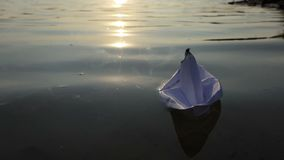 Białego papieru łódź pływa w jeziornej wodzie przy zmierzchem w mo zdjęcie wideo