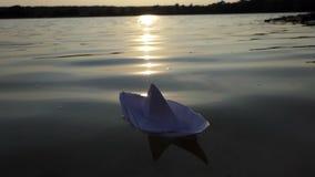 Białego papieru łódź unosi się w jeziornej wodzie przy zmierzchem w mo zbiory wideo