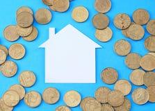 Białego papieru dom wśród monet Fotografia Stock