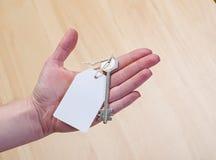Białego papieru etykietka dołączająca metalu srebra klucz w ręce Zdjęcie Royalty Free