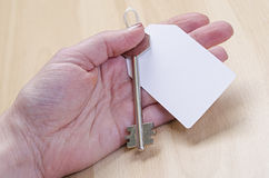 Białego papieru etykietka dołączająca metalu srebra klucz w ręce Obraz Stock