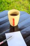 Białego papieru notatka z piórem z filiżanką na stole Obrazy Stock