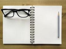 Białego papieru nutowa książka z popielatym ołówkiem i czarnymi szkłami na drewnie Fotografia Stock