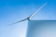 Białego silnika wiatrowego wywołująca elektryczność na niebieskim niebie Obraz Royalty Free