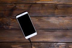 Białego telefonu komórkowego drewnianego tła drewniany ładuje kabel Zdjęcia Stock