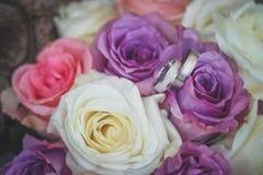 Białego złota obrączki ślubne na bukiecie purpurowe i białe róże fotografia stock