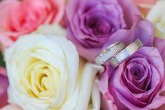 Białego złota obrączki ślubne na bukiecie purpurowe i białe róże zdjęcia stock