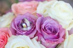 Białego złota obrączki ślubne na bukiecie purpurowe i białe róże obraz stock
