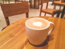 Białej filiżanki gorący capuccino z białym kierowym kubkiem na wierzchołku na brązu drewnianym stole w frontowego kontuaru barze  zdjęcie royalty free