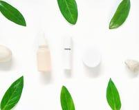 Białej kremowej butelki umieszczający, Pusty etykietka pakunek dla egzaminu próbnego up na zielonym ulistnienia tle, i kwiaty Poj fotografia stock