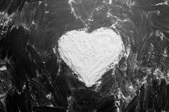 Białej mąki kierowy kształt w środku na czarnych tło tekstury rysunkach z palcem zdjęcie stock