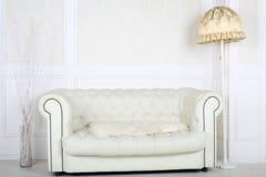 Białej skóry kanapa w pokoju z podłogową lampą Obrazy Stock