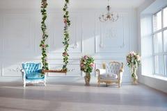 Białej skóry rocznika stylu krzesło w klasycznym wewnętrznym pokoju z dużą wiosną i okno kwitnie Zdjęcia Royalty Free