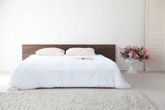 Białej sypialni jaskrawi wnętrza z łóżkiem Zdjęcie Stock