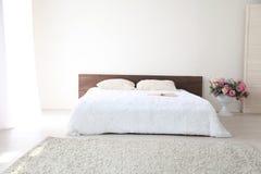 Białej sypialni jaskrawi wnętrza z łóżkiem Obrazy Royalty Free