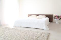 Białej sypialni jaskrawi wnętrza z łóżkiem Obraz Stock