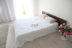Białej sypialni jaskrawi wnętrza z łóżkiem Fotografia Stock